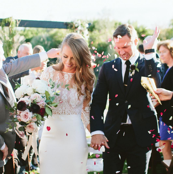 Groom swatting away petals being thrown at bride and grooms exit. Paige Jones Photos. bridesmaidsconfession.com