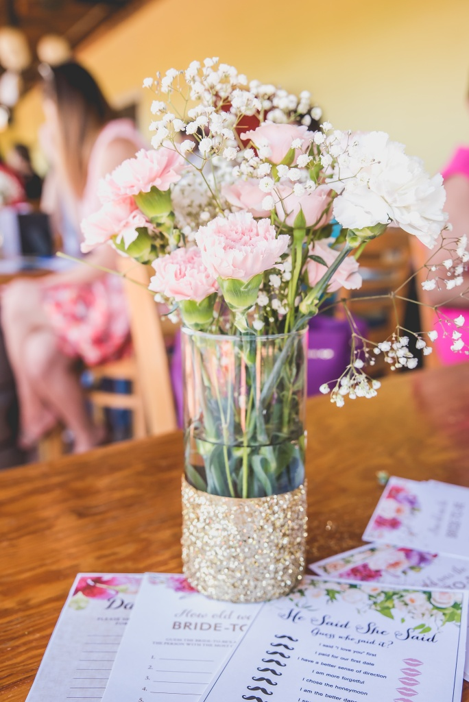 Pink and white carnations with babys breath in clear vases with gold glitter bottoms. Gorgeous centerpieces for a bridal shower.