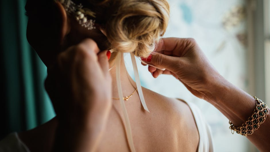 Bride getting a tie in her hair.