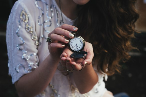 Bridesmaid holding a watch.