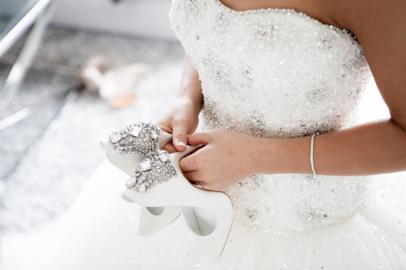 Woman holding her heels in a wedding dress.