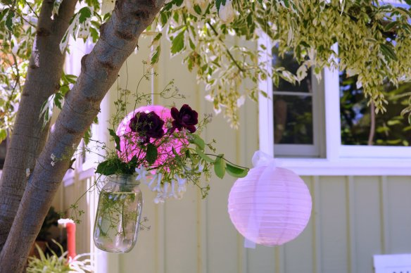 Pink lanterns and flowers in a mason jar.